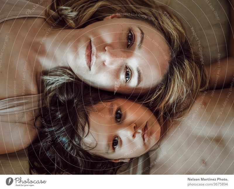 Portrait of mom and daughter lying down in the bed, hispanic and caucasian. High view. portrait love family eyes beautiful kid high view mommy Love