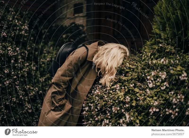 Portrait of a beautiful stylish blonde. She is wearing a green coat. She is bended in the bush. resting fashion lost frustrated no idea moody portrait woman