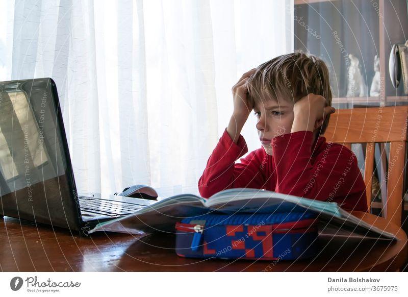 School kid in self isolation using laptop for homework, Social Distance learning online education during coronavirus epidemic. Cute boy studies and does school homework at home during quarantine
