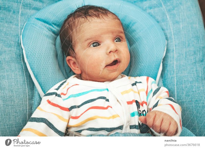 Curious and happy newborn girl in her hammock baby funny face curious adorable cute boy unisex smile smiling expressive feelings development clothes comfort