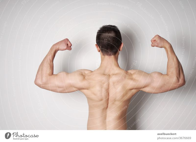 man flexing biceps and back muscles bodybuilder strength power strong arm bodybuilding male muscular fit fitness athletic athlete sports shirtless masculine