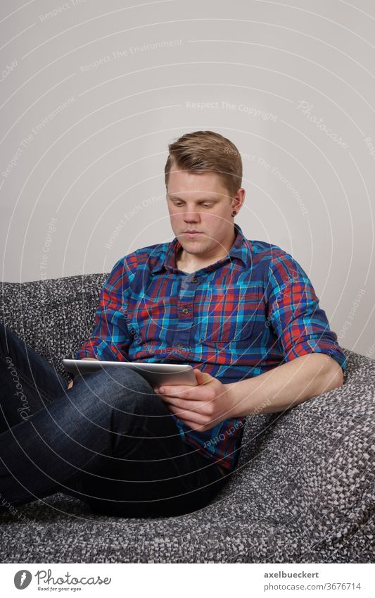 young man using tablet computer woman girl entertainment e-learning sofa couch pc student smiling home living room lifestyle holding sitting relaxing reading