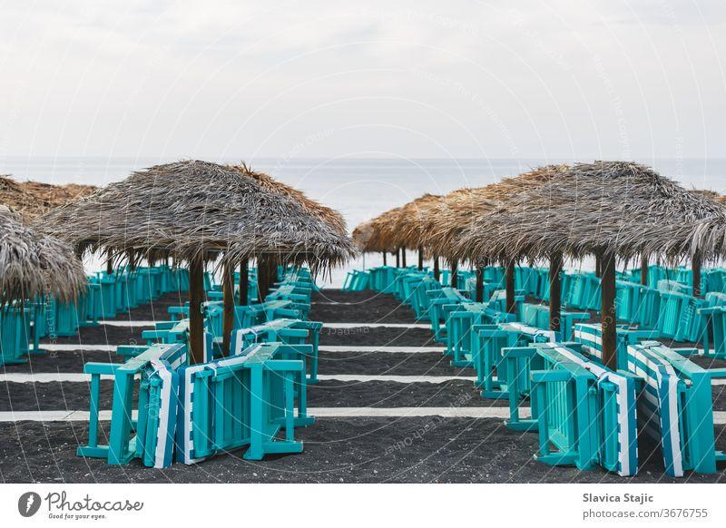 Sunbeds and parasols on blank sand beach. Perissa, Santorini island, Greece aegean beachside black blue caldera coast coastline cyclades destination europe