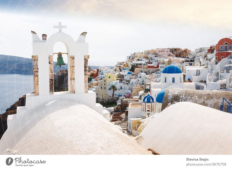 View of sea and Oia village  through traditional Greek white church arch with cross and bells in Oia village of Cyclades Island, Santorini aegean architectural