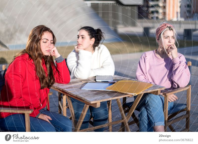 Angry friends or roommates sitting in a cafe outdoors 3 angry upset friendship arguing female girls woman together unhappy disagreement argument fight teenager