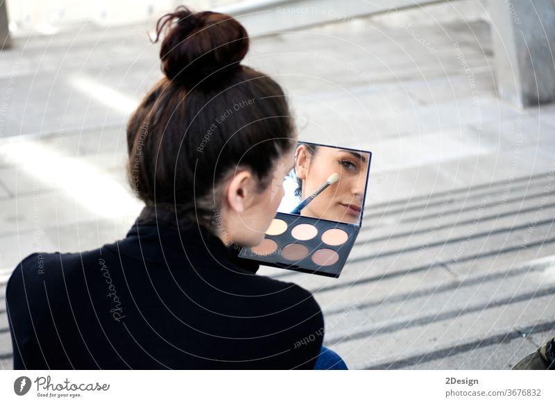 Rear view of a young woman with ponytail sitting on steps outdoors while using a makeup brush day make-up adult one person beauty lifestyle photography applying