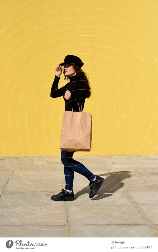 Fashion portrait woman with shopping bags wearing black outfit with hat posing on yellow wall. female girl sale happy beautiful adult fashion shopaholic young