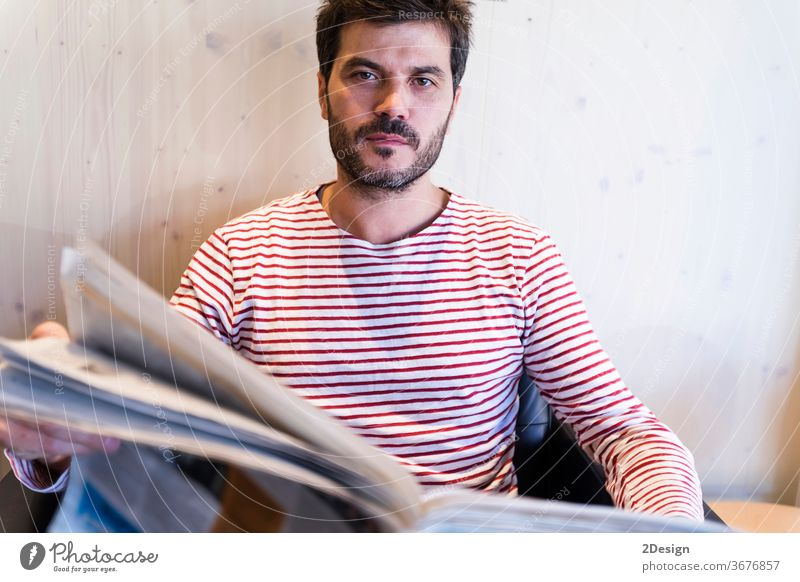 Adult man reading newspaper sitting in sofa 1 male people indoor lifestyle caucasian business beard portrait photogenic home person attractive smile senior