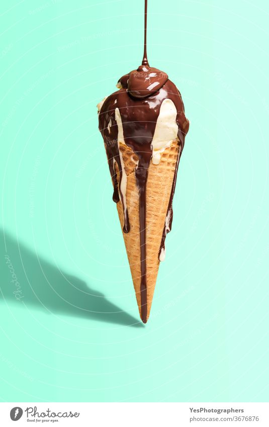 Vanilla ice cream cone with dripping chocolate. Ice cream with topping. Melted chocolate drip background bright color copy space cut out dairy delicious dessert