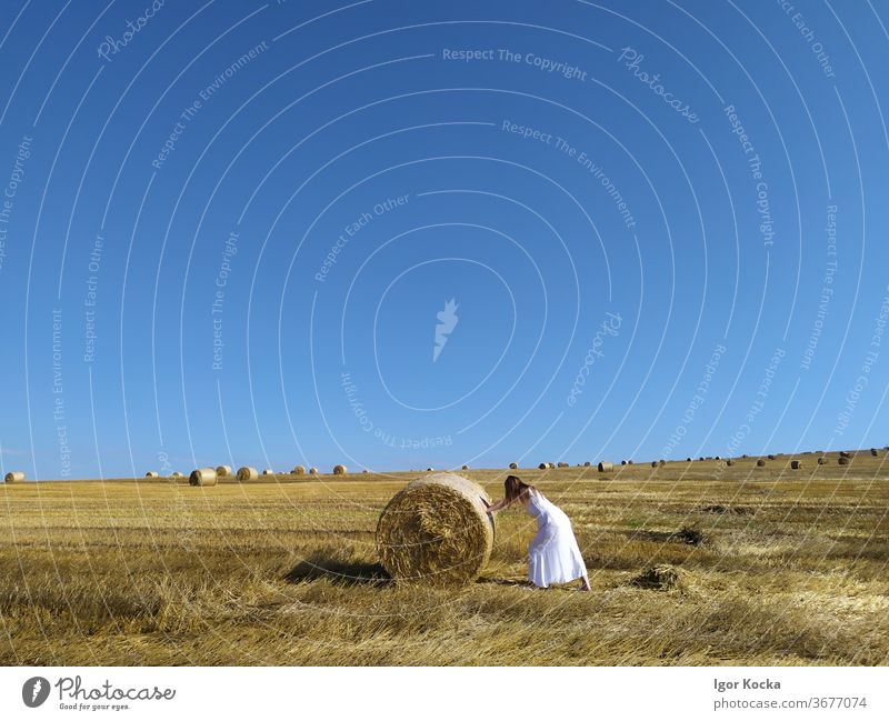 Woman Pushing Hay Bale In Field Hay bale rolling Sky Sunlight scenic Agriculture Farm Harvest Rural Summer