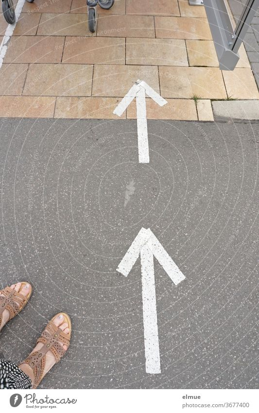 two care panels on the floor indicate shopping trolleys, two feet in sandals are visible on the edge Arrow Shopping Regulation direction of arrow everyday life