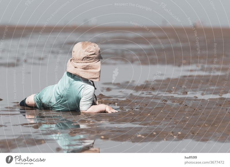 the little boy lies comfortably in the mudflats and looks around Toddler Child Playing Boy (child) Beach Mud flats Low tide North Sea Ocean Coast Water Horizon