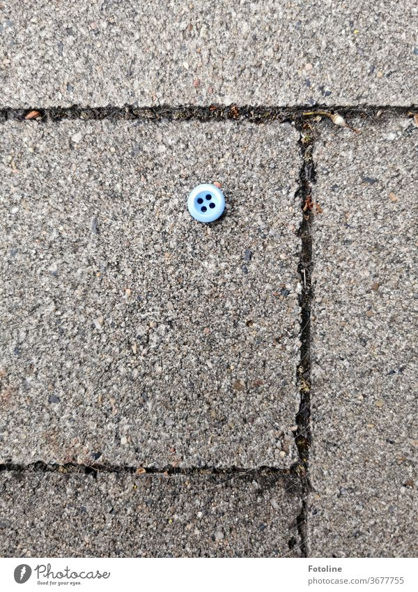 Jim Knopf - or a small blue button lies on the cobblestones of a sidewalk knob Detail Colour photo Clothing Fashion Blue Deserted Close-up Day