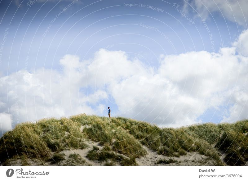 Man stands alone in the dunes and enjoys the peace and quiet Stand To enjoy tranquillity Lonely gap vacation Clouds Small huge landscaping landscape photograph