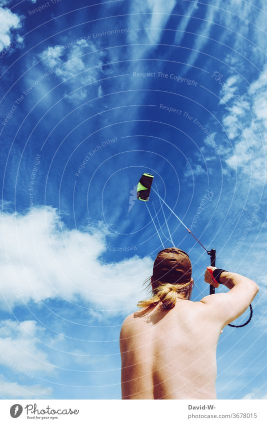 Man flies a kite in bombproof weather kites cause to rise climb the kite Young man Worm's-eye view Blue Sky Clouds Summer hobby Wind Dragon Playing Air