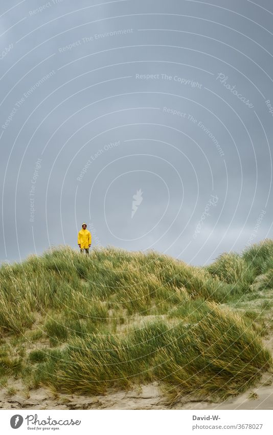 Man in yellow raincoat stands ready in the dunes for the storm that is about to arrive friesennerz Dike Thunder and lightning Storm Wet downpour Yellow vacation