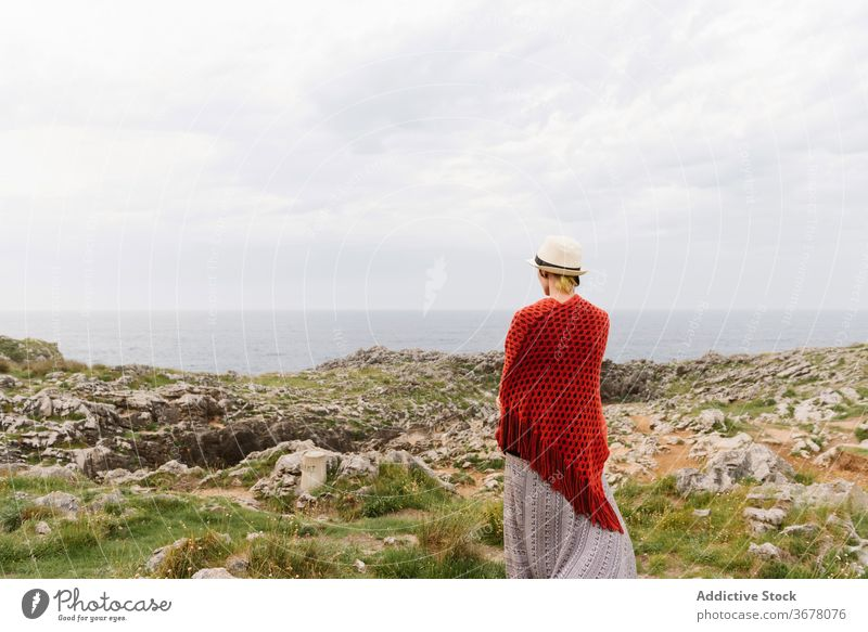 Stylish woman standing near cliff on sea coast travel rocky nature style explore spain asturias adventure wanderlust trendy calm alone wild activity llanes