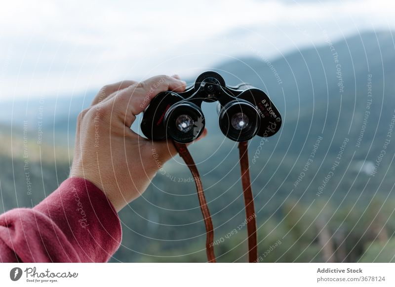 Traveler exploring nature with binoculars mountain explore hike travel activity discovery observe adventure location forest trekking hand lens optical