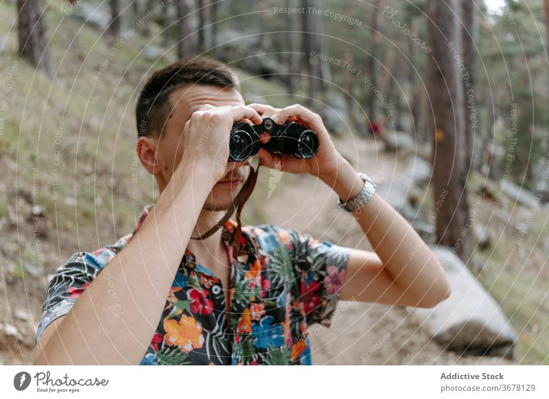 Traveler exploring nature with binoculars in forest man hike mountain explore travel activity trekking young discovery adventure spain navacerrada madrid male