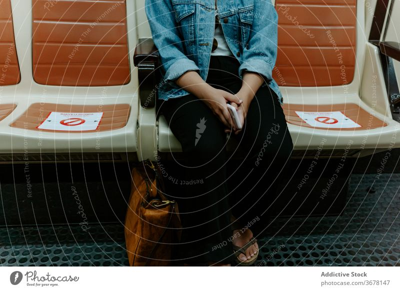 Woman sitting in subway wagon with marking for keeping distance coronavirus metro passenger woman social distancing covid pandemic restriction infection female