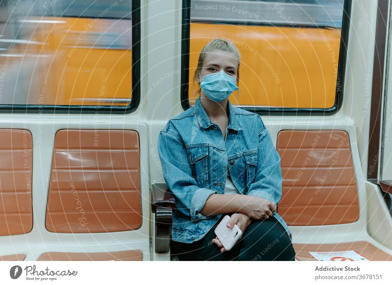 Young woman in protective mask in subway train coronavirus passenger metro social distancing covid pandemic restriction infection female seat alone underground