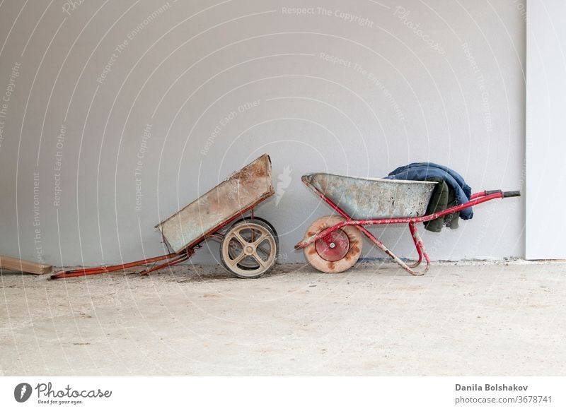 old construction cart and wheelbarrow on the background of a stucco wall construction trolley container retro single wheel vintage gardening metal industry