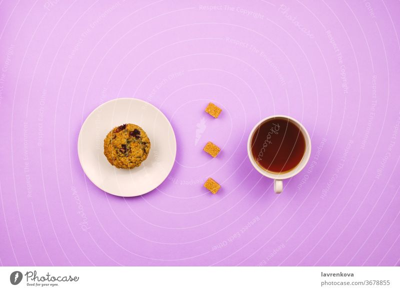 Flatlay with a blueberry muffin, cup of tea and cane sugar cubes. Breakfast concept. Violet background. fresh caffeine bakery violet drink cappuccino dessert