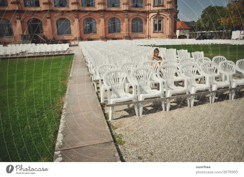 girl sits alone in a seated area in the open air and waits for the show to begin, which was cancelled due to corona chairs Lawn Without audience Deserted