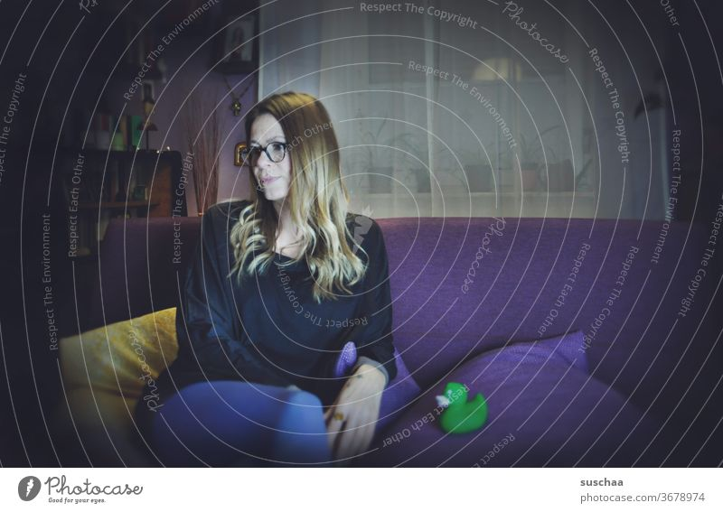 woman on a purple sofa with a green bath duck on the sofa cushion Woman at home Stayhome Living room couch Strange togetherness Whimsical Hair and hairstyles