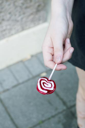 hand holding a lolly Lolly lollipop by hand Youth (Young adults) teenager Child Lick candy Sugar Infancy Sweet Xylitol tooth-friendly Dentist Candy Delicious