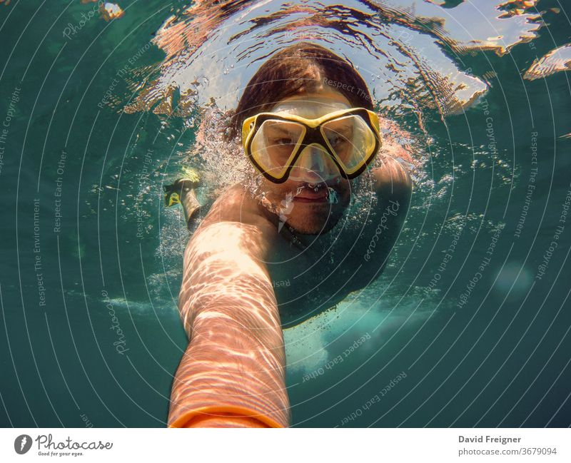 Young man with snorkel and diving mask swimming and taking a selfie under water. Travel, vacation and sports activity concept. ocean young sea underwater diver