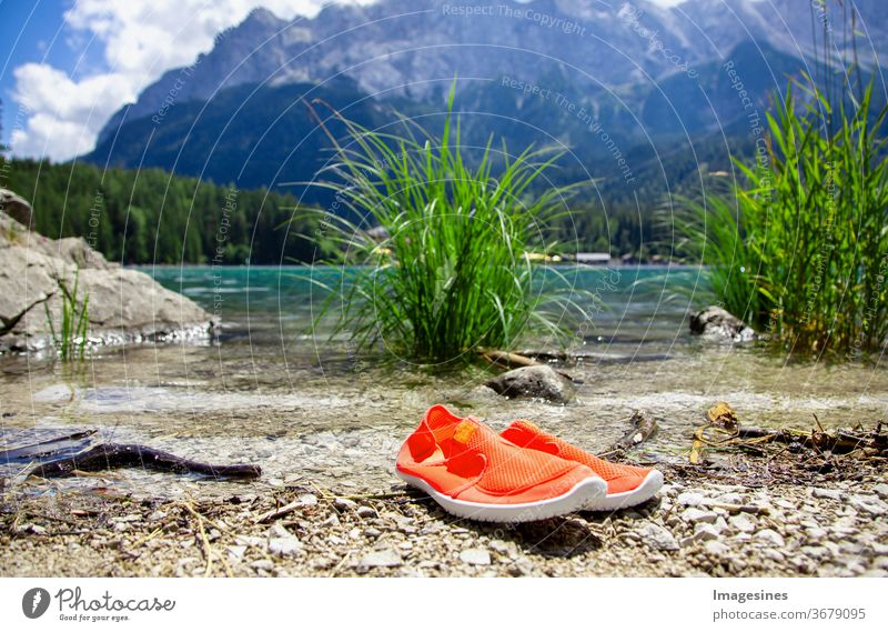 Bathing shoes at the Eibsee shore in the Bavarian Alps near Garmisch Partenkirchen, Bavaria Germany. View of the Wetterstein mountain range. Wetterstein mountain range Zugspitze