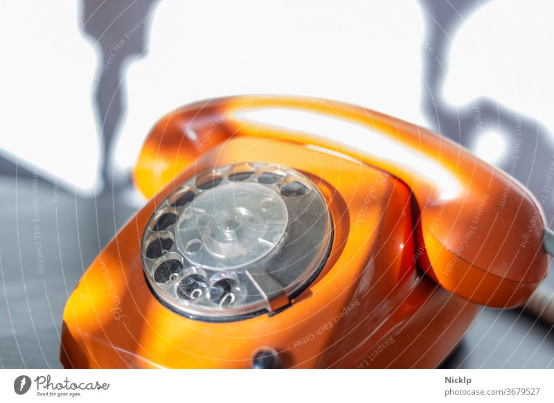 "Telephoning - orange telephone ""FeTAp 615"" in orange with dial and handset (retro) in bright sunlight Telephone dial telephone Rotary dial Retro Orange fetap"