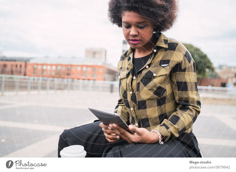 Afro american latin woman using digital tablet afro people young female technology coffee casual computer person beautiful bench internet city lifestyle smile