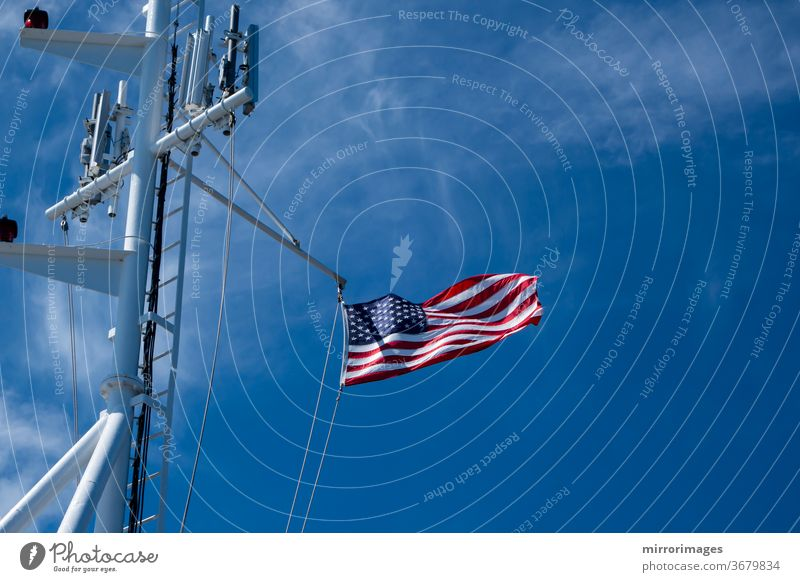 United States of America Flag Blowing in the Wind on the the deck of a large ship at sea with cell towers america american banner battleship blue boat breeze