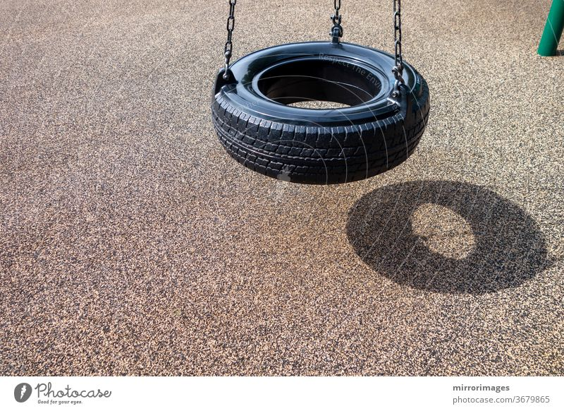 black chain Tire Swing at a children's  play ground no people activity background black chain tire swing chains childhood children swing empty empty swings