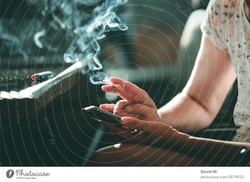 Woman with a cigarette in her hand typing on her cell phone mobile Typing by hand hands Fingers Smoking Smoke smoke Addiction Addictive behavior addictive