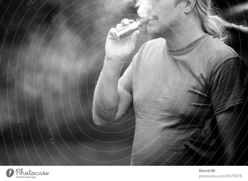 Man pulls an e-cigarette e-zigarette Cigarrete Electric Electronic Dependence drugs Addiction addictive potential addicted be dependent Black & white photo