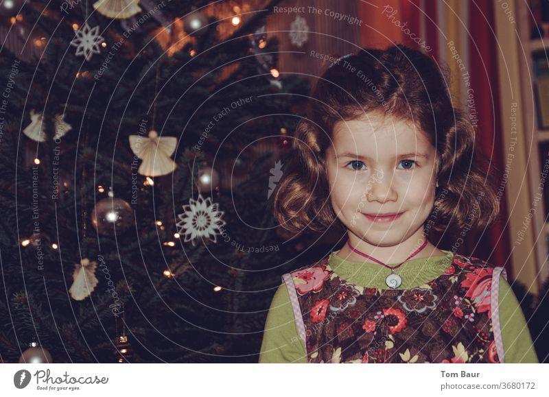 Portrait of a girl in front of the Christmas tree portrait Angel christmas tree blonde hair Looking into the camera cheerful Happiness Festive