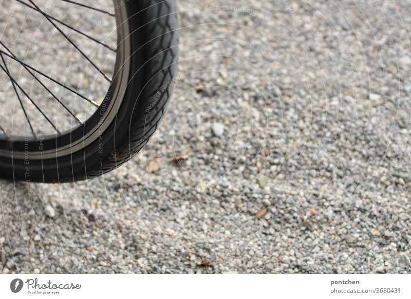 Part of a bicycle tyre on gravel. Mobility Bicycle Bicycle tyre turnaround Gravel Environmental protection Spokes Sports Monochrome out Cycling
