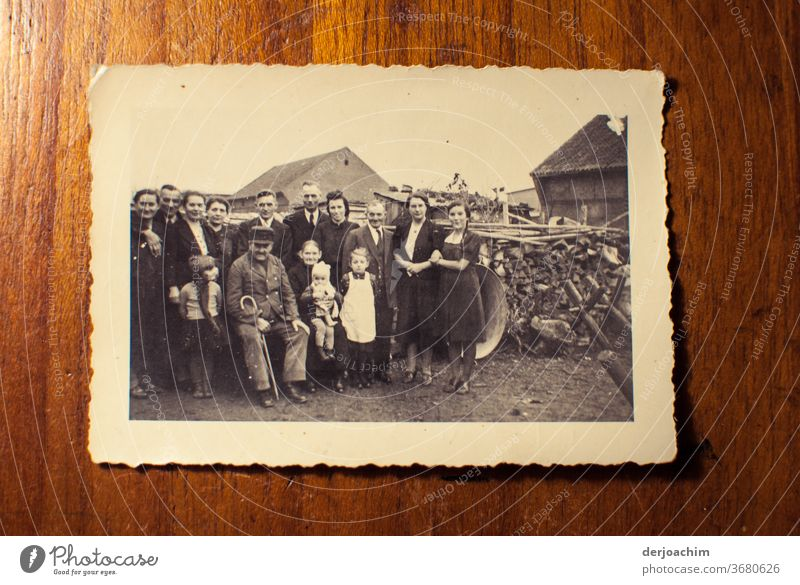 Family photo in the countryside. All standing around the grandfather , and grandmother . In the background a woodpile . Very old photo of the family in the country. East Prussian impressions