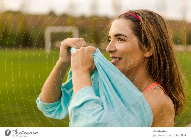 Wear something warm women portrait beautiful fitness outdoor clothes jacket wear park relax grass field 30s gymwear health healthy athletic smile happy sporty