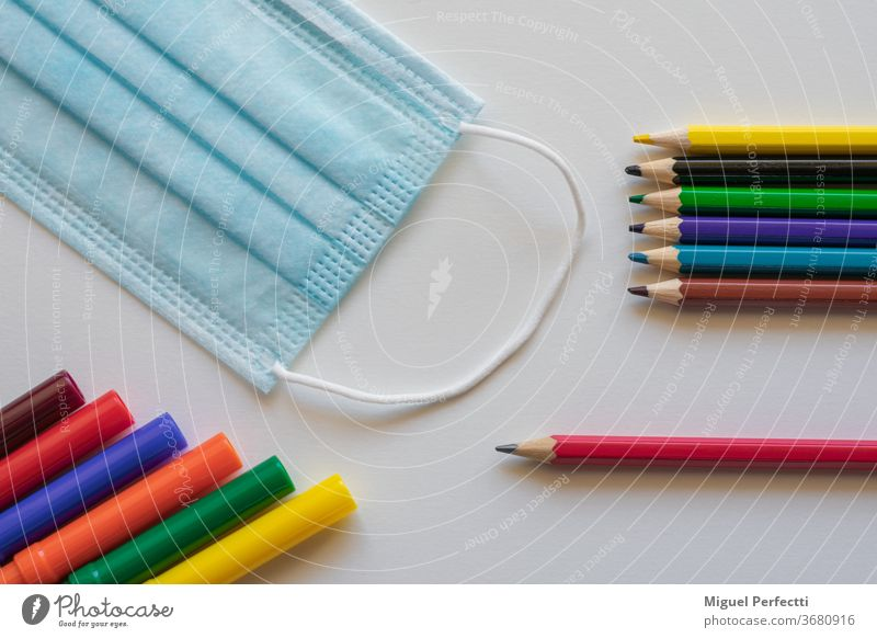Markers and coloured pencils next to a mask, which are mandatory in many countries to prevent Covid 19 infections in schools back to school Markings crayons