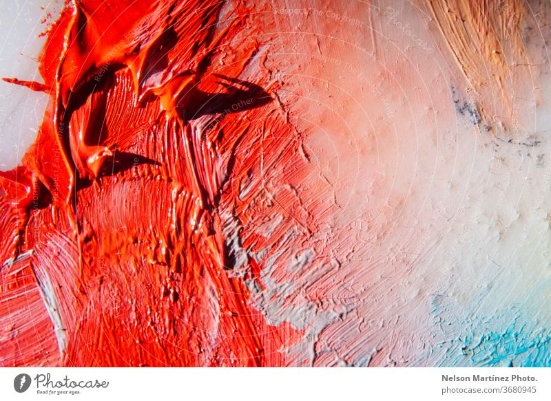 Close-up of a color palette of a painter. Red, orange, white and blue colors. A closeup shot of the red paint mixed up with white paint on the canvas.
