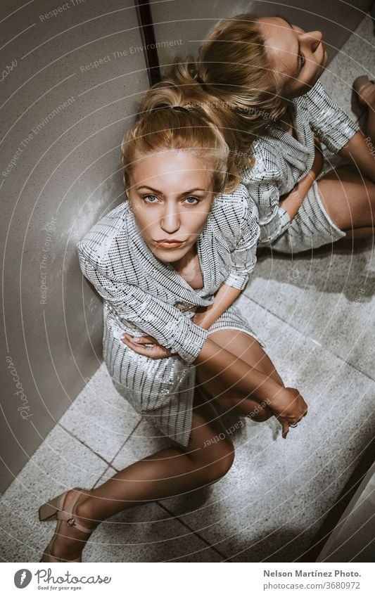 Beautiful blonde model sitting in the corner. She has a serious expression and is wearing a stylish white dress. High view. luxury fashion caucasian portrait