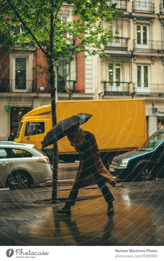 Stylish blonde woman walking in the rain. She is holding a black umbrella in an unban area. rainny Rain Umbrella Weather Wet Human being Bad weather Water
