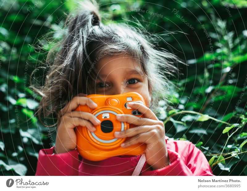 Little hispanic girl holding an Instax orange camera. Vintage camera. She is in front of a green background. kid little girl photography leasure fun colorful