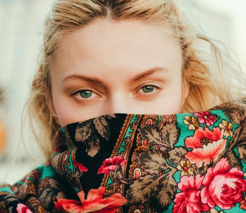 Portrait of a causasian blonde.  She is looking directly at the camera covered in a floral patterned scarf. portrait caucasian Woman Portrait photograph