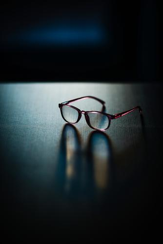 glasses are on the table Eyeglasses Know Lie Table is reflection mirror Shadow nearsighted age Image go blind Reading aid Person wearing glasses Spectacles
