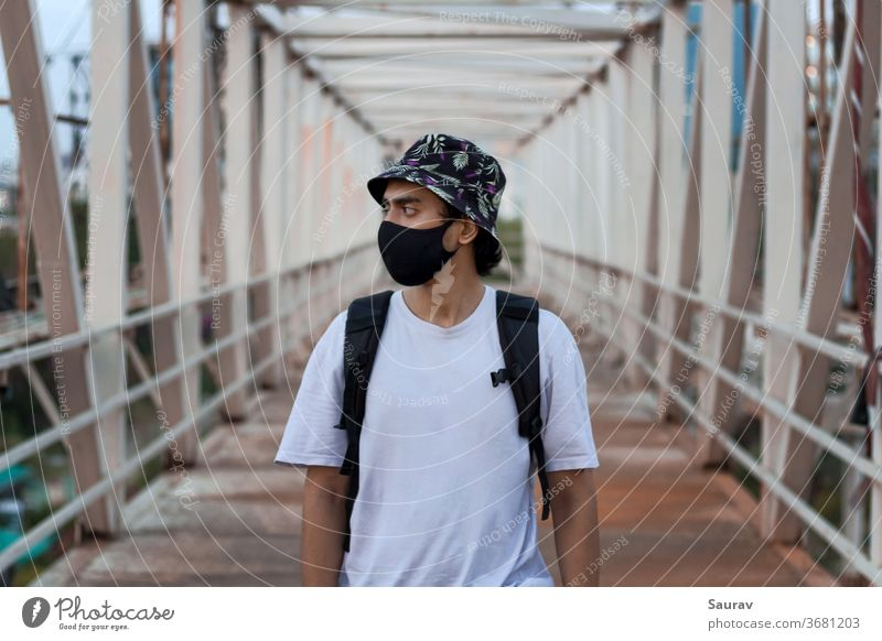 Portrait of a Young Millennial on a Foot Bridge Outdoors Wearing a Black Protective Face Mask to Prevent Covid-19 Virus Infection in a City. The New Normal.